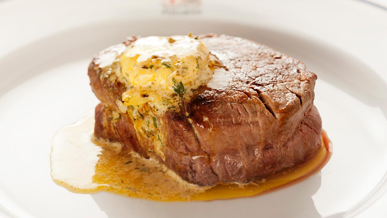Steak with butter on a Pullman-branded plate