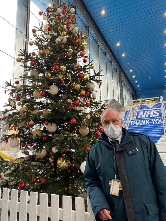 GWR staff member Pat Kemp in front of Christmas tree