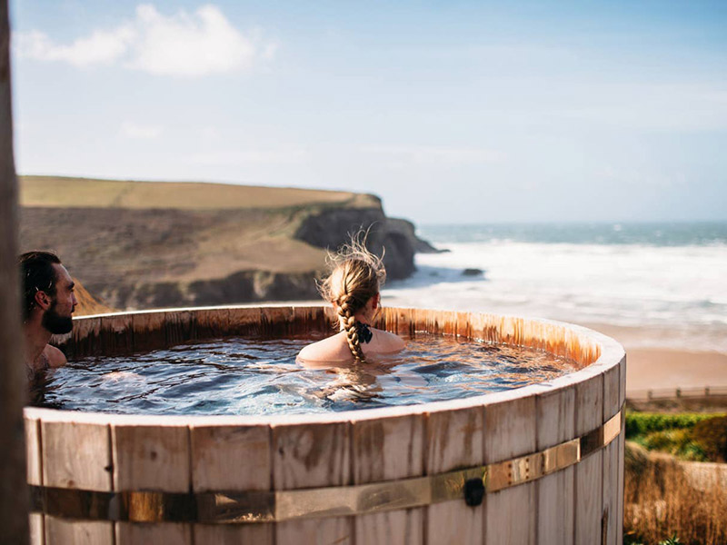 Couple in a hot tub at The Scarlet, Cornwall